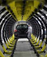 A Serbian factory worker looks at a Fiat 500 L car in the assembly hall in the new Fiat factory, in Kragujevac, some 100 kilometers (70 miles) south of Belgrade, Serbia, Monday, April 16, 2012. Italian carmaker Fiat has opened a production line in Serbia