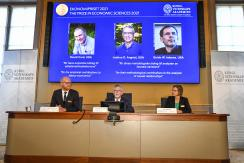 Permanent Secretary of the Royal Swedish Academy of Sciences Goran K Hansson, center, announces the 2021 Nobel prize for economics, flanked by members of the Royal Swedish Academy of Sciences Peter Fredriksson, left, and Eva Mork, during a press conferenc