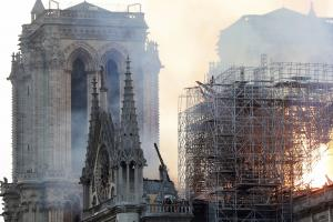Firefighters tackle the blaze as flames and smoke rise from Notre Dame cathedral as it burns in Paris, Monday, April 15, 2019. Massive plumes of yellow brown smoke is filling the air above Notre Dame Cathedral and ash is falling on tourists and others aro