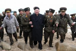 In this March 7, 2013 photo released by the Korean Central News Agency (KCNA) and distributed March 8, 2013 by the Korea News Service, North Korean leader Kim Jong Un, center, walks with military personnel as he arrives for a military unit on Mu Islet, lo